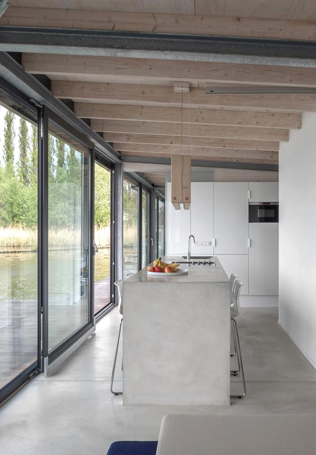 Z betonowej podłogi wyrasta betonowa wyspa kuchenna.